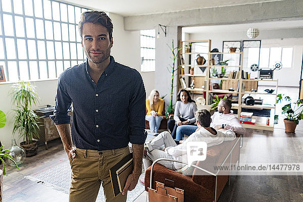 Portrait of confident young businessman with coworkers in background in loft office