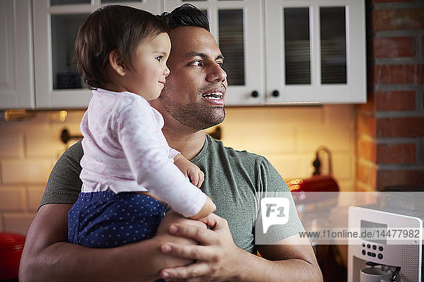 Father holding baby girl in kitchen at home