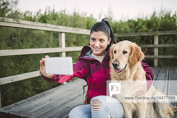 Smiling young woman taking a selfie with her dog