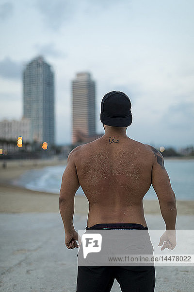 Rear view of barechested muscular man on the beach at dusk