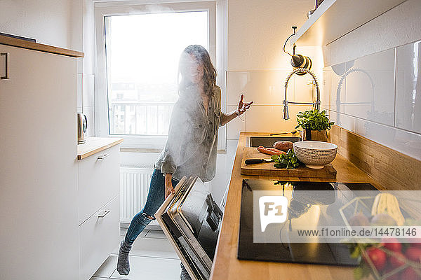 Woman opening steaming dish washer in the kitchen