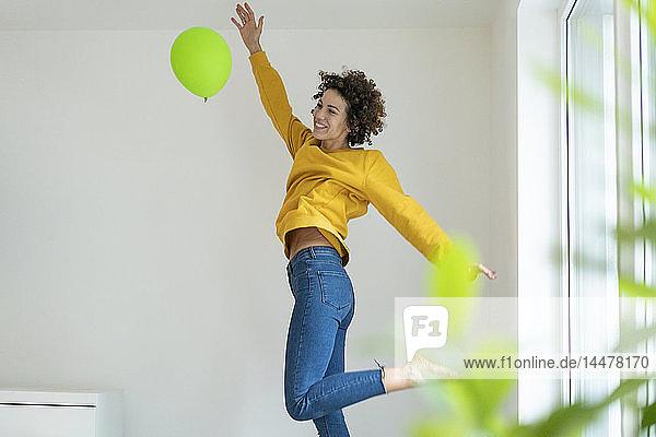 Glückliche Frau spielt zu Hause mit einem Luftballon