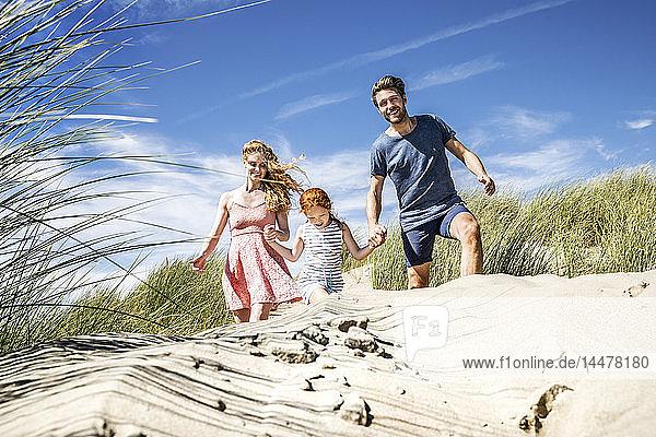 Niederlande  Zandvoort  glückliche Familie mit Tochter in Stranddünen