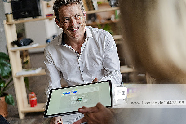 Smiling businessman holding tablet with a mind map during a presentation in loft office