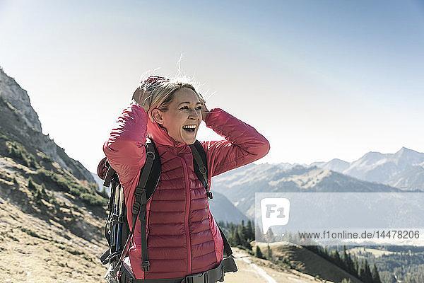 Österreich  Tirol  glückliche Frau auf einer Wanderung in den Bergen  die die Aussicht genießt