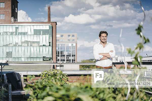 Geschäftsmann  der in seinem städtischen Dachgarten Pflanzen anbaut