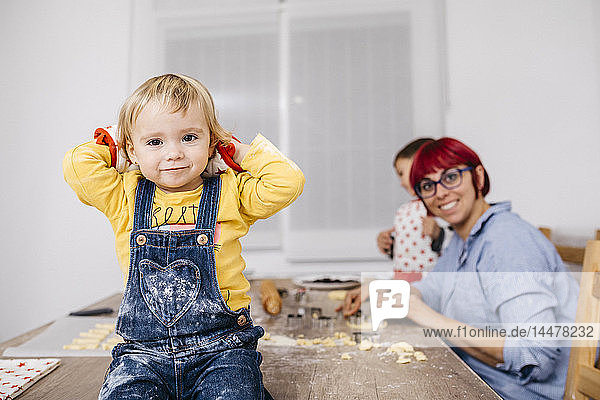 Portrait of smiling toddler girl sitting on kitchen table where mother and brother preparing cookies