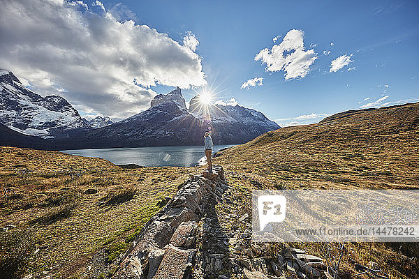 Chile  Torres del Paine National park  woman standing on rock in front of Torres del Paine massif at sunrise