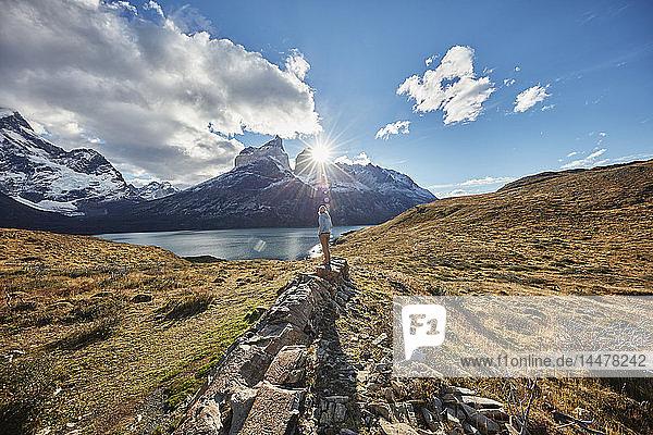 Chile  Torres del Paine Nationalpark  Frau steht bei Sonnenaufgang auf einem Felsen vor dem Torres del Paine Massiv