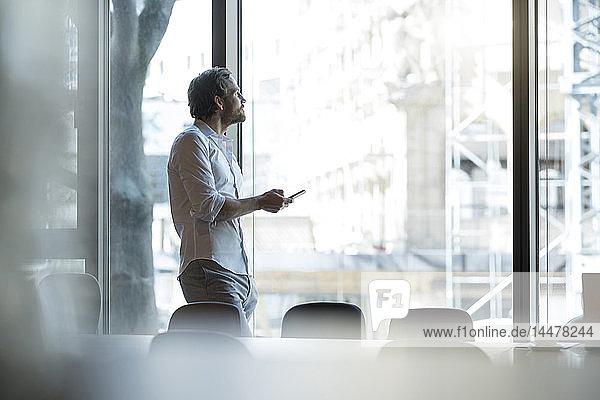 Lächelnder  lässiger Geschäftsmann lehnt an Wand in Lounge-Bereich mit Smartphone