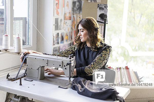 Junge Designerin mit Nähmaschine in einem Atelier