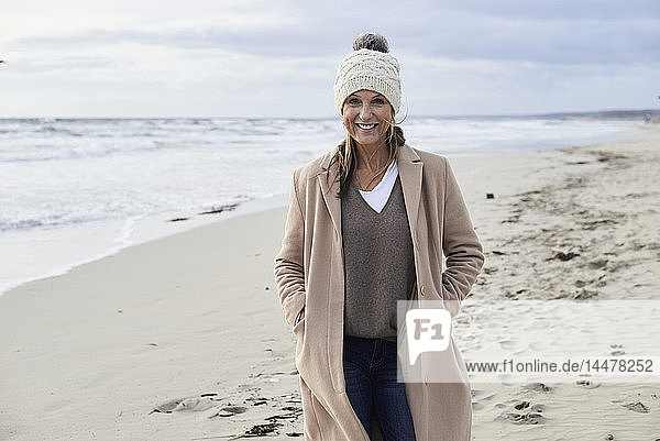 Spain  Menorca  portrait of smiling senior woman wearing bobble hat and coat on the beach in winter