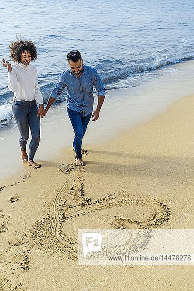 Spanien  Barcelona  glückliches Paar am Strand  das sich am Strand vergnügt und ein Herz in den Sand zeichnet