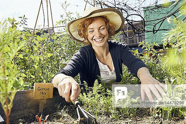 Glückliche junge Frau mit Strohhut im Stadtgarten