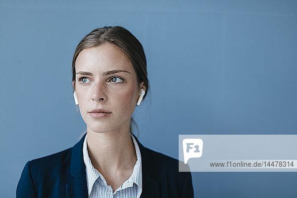 Porträt einer jungen Geschäftsfrau vor blauem Hintergrund  die Ohrknöpfe trägt