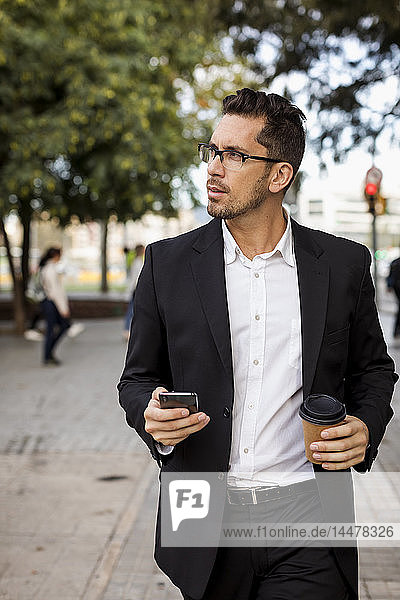 Businessman with takeaway coffee and cell phone in the city on the go