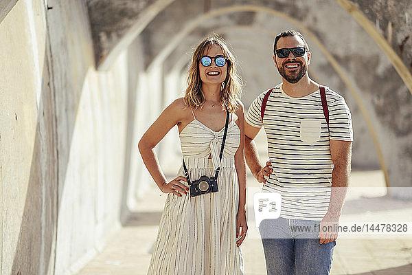 Spanien  Andalusien  Malaga  glückliches Touristenpaar  das unter einem Torbogen in der Stadt steht