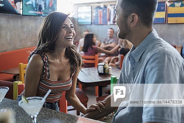 Glückliches Paar beim geselligen Beisammensein in einer Bar