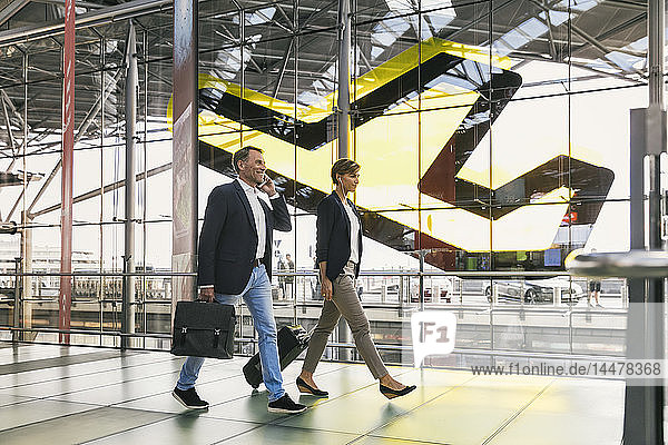 Businessman on cell phone and businesswoman walking at the airport