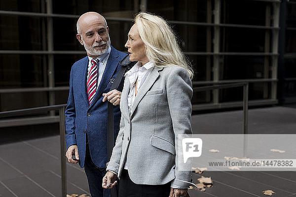 Ein älterer Geschäftsmann und eine Geschäftsfrau gehen und sprechen in einem Foyer