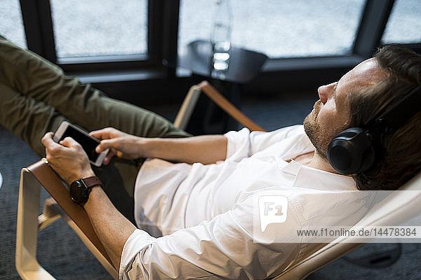 Lässiger Geschäftsmann  der sich im Lounge-Bereich eines Coworking Space entspannt und Musik hört