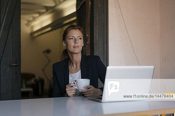 Nachdenkliche Geschäftsfrau sitzt am Schreibtisch im Büro mit Tasse Kaffee und Laptop