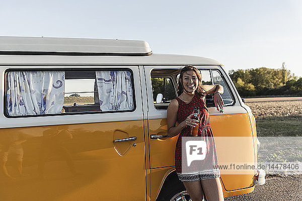 Pretty woman on a road trip with her camper  taking a break at sunset