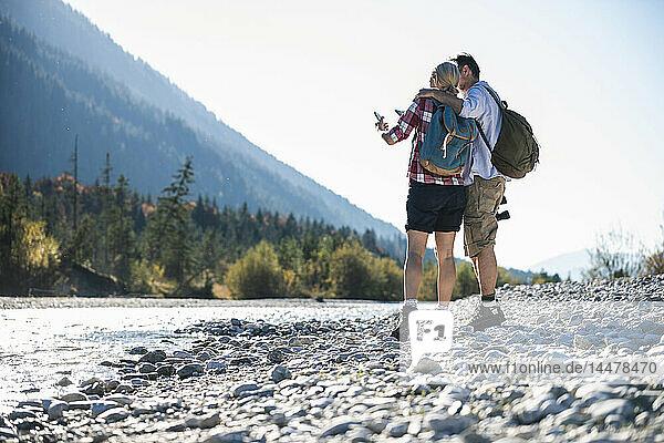 Österreich  Alpen  Ehepaar auf Wanderung mit Blick aufs Handy