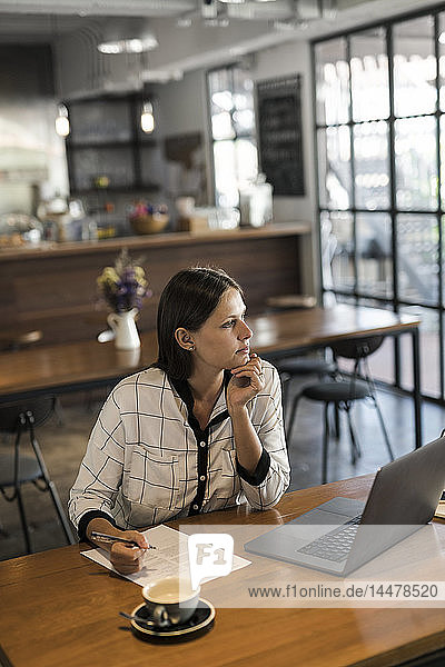 Young businesswoman in a cafe writing on paper and working with laptop on wooden table