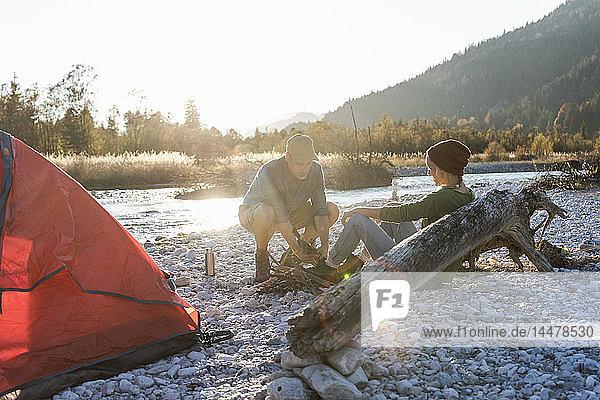 Ein erwachsenes Paar zeltet am Flussufer und sammelt Holz für ein Lagerfeuer