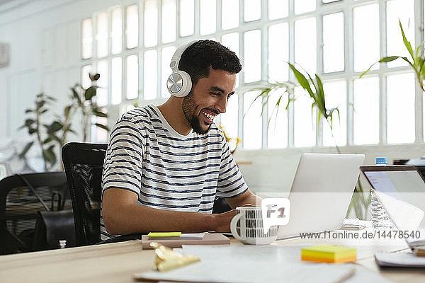 Lachender junger Mann mit Kopfhörer und Laptop am Schreibtisch im Büro