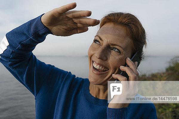 Deutschland,  Hamburg,  lachende Frau am Elbufer am Handy
