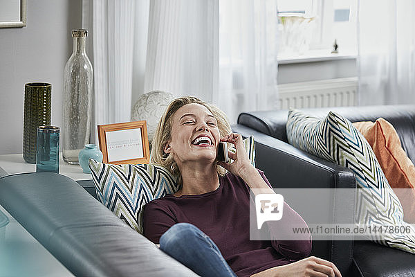 Laughing young woman on cell phone lying on couch at home