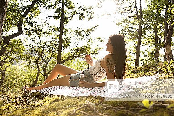 Lächelnde junge Frau im Wald auf einer Decke liegend mit Getränk und Apfel