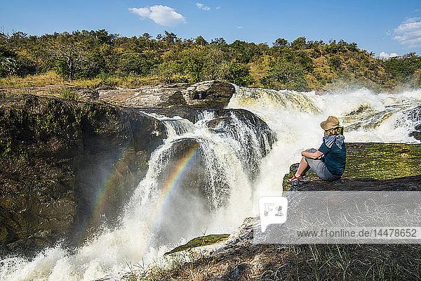 Afrika  Uganda  Frau blickt auf die atemberaubenden Murchison Falls  am Nil  Murchison Falls National Park