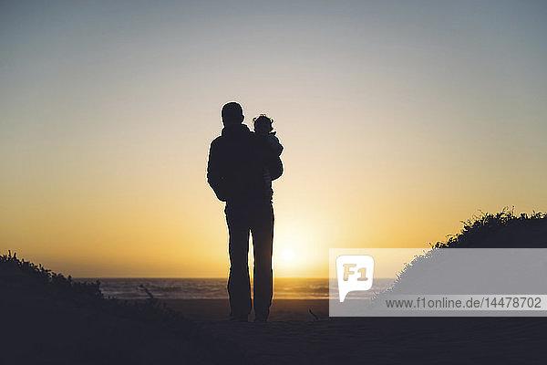 USA  Kalifornien  Morro Bay  Silhouetten von Vater und Baby beim Sonnenuntergang am Strand