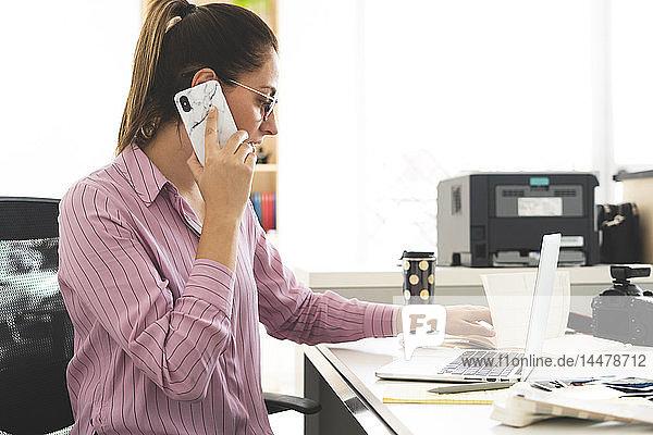 Designer im Büro arbeiten  Laptop benutzen  telefonieren