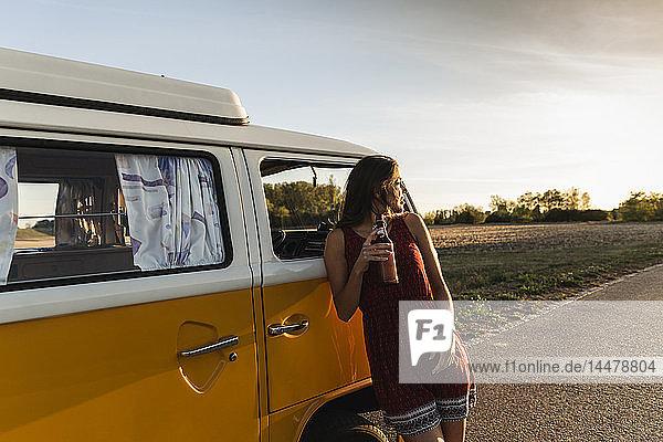 Hübsche Frau auf einer Autoreise mit ihrem Wohnmobil  die bei Sonnenuntergang eine Pause macht