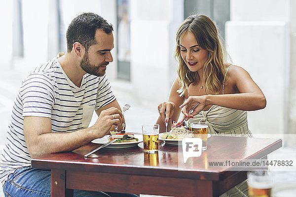 Ein Paar isst und trinkt Bier in einem Restaurant auf der Straße