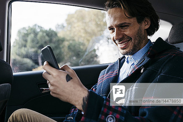 Smiling man sitting on back seat of a car using cell phone