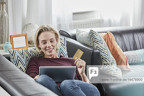 Happy woman with tablet and credit card lying on couch at home