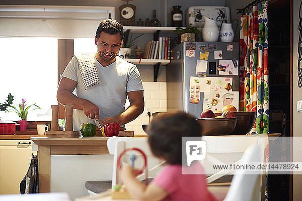 Lächelnder Vater bereitet zu Hause in der Küche Essen für seine Tochter zu
