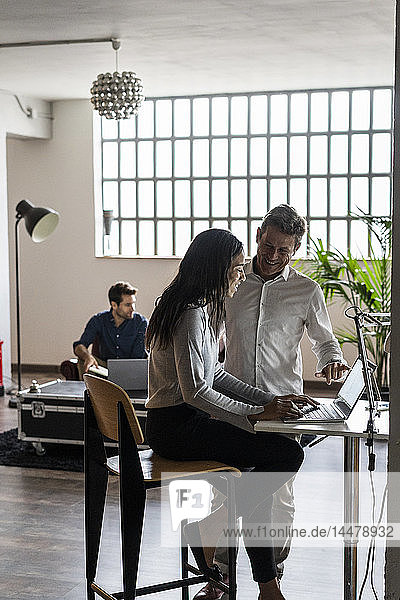 Smiling businessman and businesswoman using laptop in loft office