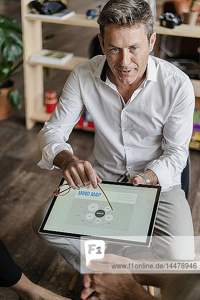 Businessman explaining a mind map on tablet screen during a presentation in loft office