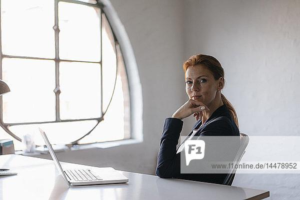 Porträt einer Geschäftsfrau mit Laptop  die am Schreibtisch im Büro sitzt
