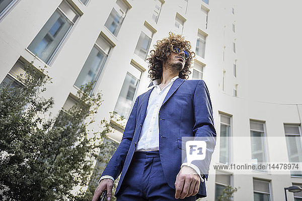 Junger modischer Geschäftsmann mit lockigem Haar  der einen blauen Anzug und eine Sonnenbrille trägt