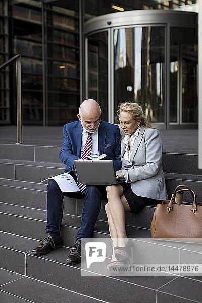 Leitender Geschäftsmann und Geschäftsfrau sitzen mit Laptop und Diagrammen auf der Treppe