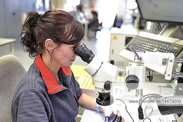 Frau  die ein Mikroskop für die Qualitätskontrolle bei der Herstellung von Leiterplatten für die Elektronikindustrie benutzt
