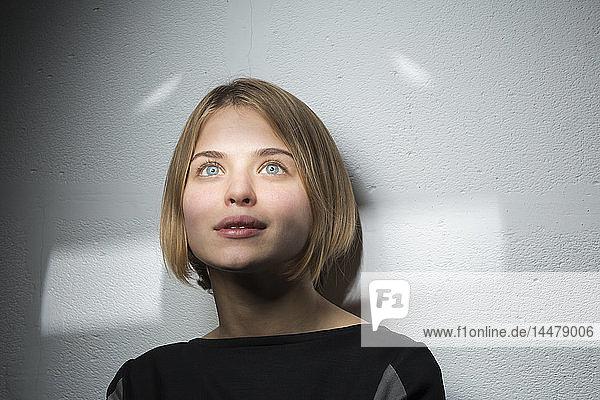 Porträt einer blonden jungen Frau mit Bob-Frisur  die aus der Ferne betrachtet wird