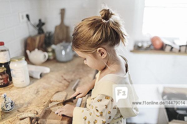 Kleines Mädchen  das in der Küche Brot schneidet